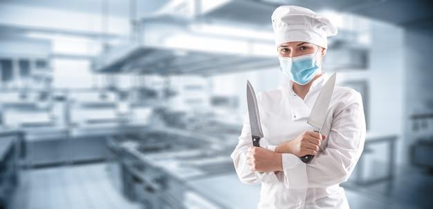 Bandeira panorâmica de um chef com máscara devido à pandemia de covid-19 em pé com as mãos cruzadas e segurando duas facas afiadas em frente à cozinha do restaurante.