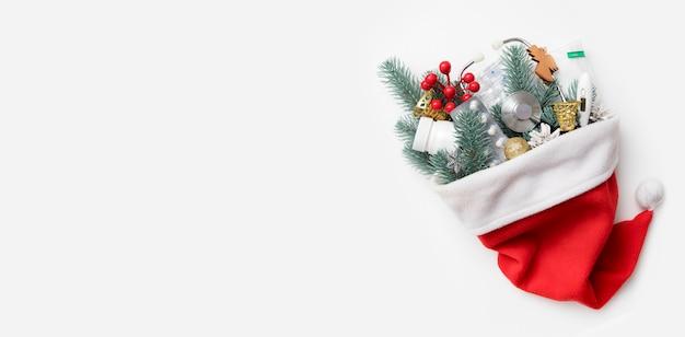 Bandeira plana leiga de natal médica com chapéu de papai noel e um estetoscópio, pílulas, termômetro e uma decoração de ano novo nele em fundo branco com espaço de cópia.