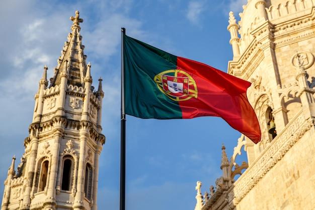 Bandeira portuguesa acenando na frente de um céu azul e um mosteiro.