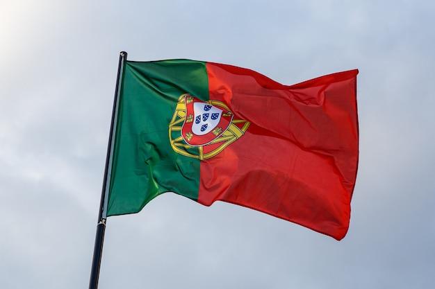Bandeira portuguesa em evolução, nuvens no céu azul