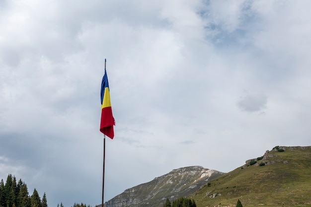 Bandeira romena no mastro da bandeira soprando no vento isolado no céu azul