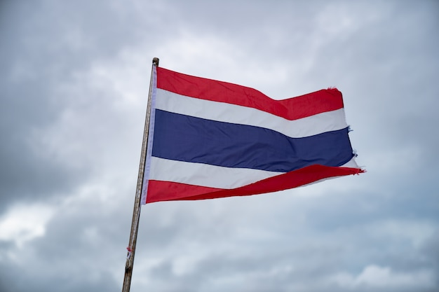 Bandeira tailandesa com céu nublado