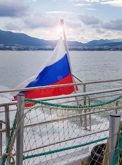 Bandeira tricolor russa em um navio, no contexto do mar e da costa com uma cidade costeira, amanhecer, verão.