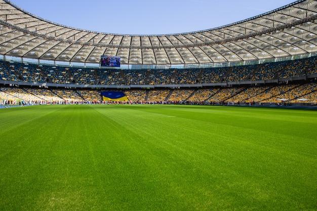 Bandeira ucraniana e multidão de pessoas no estádio olímpico de futebol com bancos amarelos e azuis