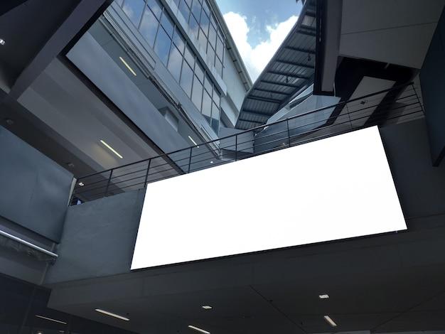 Bandeira vazia do cartaz dentro da exposição do buildingt o quadro de avisos branco para o anúncio da promoção e a informação de propaganda do negócio zombam acima.