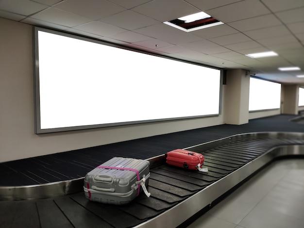 Bandeira vazia do cartaz sobre a exposição da correia da bagagem o quadro de avisos branco para o anúncio da promoção e a informação de propaganda do negócio zombam acima.