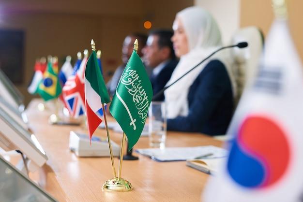 Bandeira verde do país muçulmano e tricolor uma na mesa comprida com vários delegados participando da conferência ou fórum