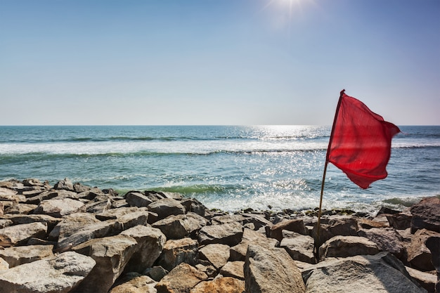 Bandeira vermelha na praia rochosa