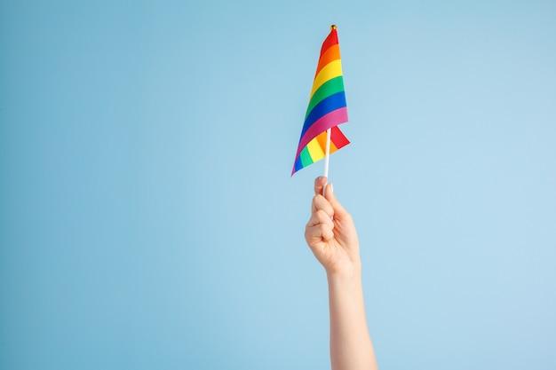 Bandeiras alegres na mão das mulheres no fundo cinza