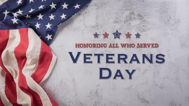 Bandeiras americanas do conceito do feliz dia dos veteranos contra um fundo de pedra escura 11 de novembro