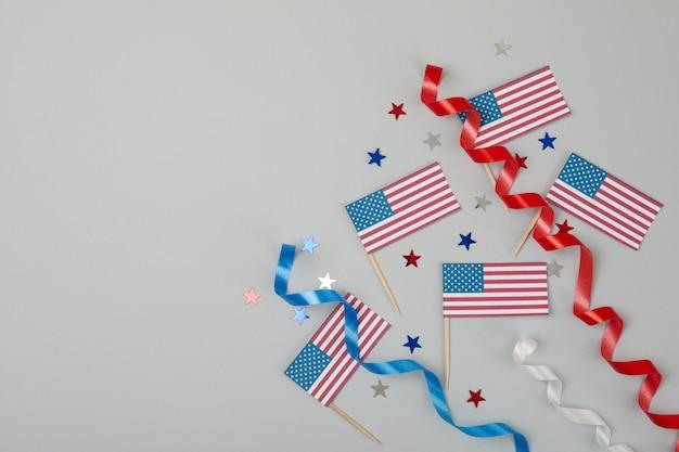 Bandeiras americanas, fitas encaracoladas e estrelas na superfície cinza