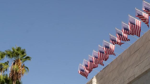 Bandeiras americanas, prefeitura de los angeles, califórnia eua. palms and star-spangled banners, stars and stripes. atmosfera de patriotismo, centro cívico municipal. autoridade do governo federal e democracia