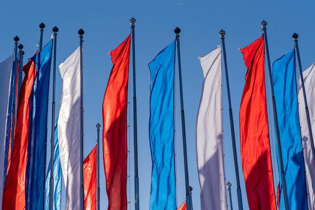 Bandeiras brancas, azuis e vermelhas como a bandeira russa no total. bandeira de imitação da rússia em uma rua durante um dia quente de sol.