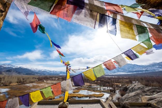 Bandeiras budistas coloridas da oração no marco bonito de leh ladakh da montanha de leh em india.