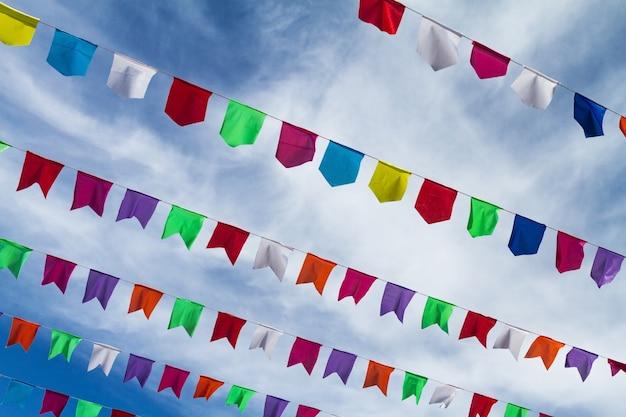 Bandeiras coloridas bonitos pequenas na corda que pendura fora para o feriado com o fundo branco brilhante das nuvens do céu azul. itália, sardenha.