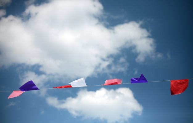 Bandeiras coloridas contra o céu azul com nuvens brancas