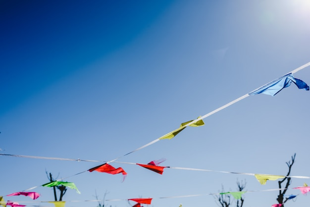 Bandeiras coloridas contra o sol balançando ao vento em uma festa ao ar livre.