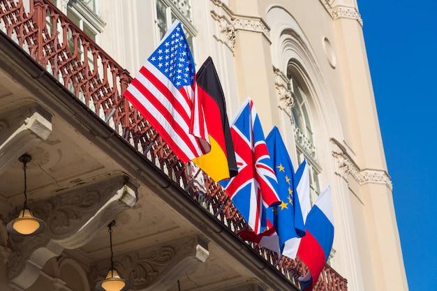 Bandeiras coloridas de diferentes países na construção contra o céu azul. eua, rússia, ue, grã-bretanha, alemanha