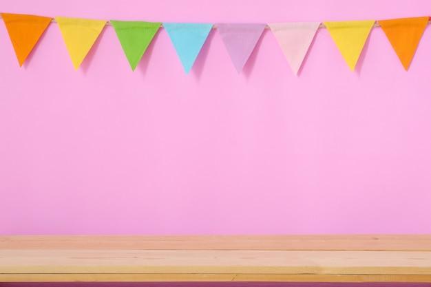 Bandeiras coloridas do partido no fundo cor-de-rosa e na tabela de madeira