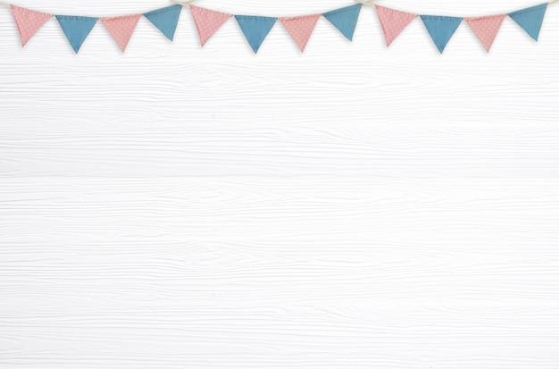 Bandeiras coloridas do partido que penduram na madeira branca em branco