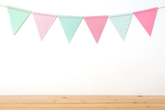 Bandeiras coloridas do partido que penduram no fundo branco da parede e no fundo de tabela de madeira