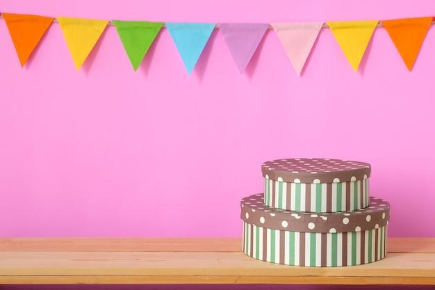Bandeiras coloridas do partido que penduram no fundo cor-de-rosa e caixa de presente na tabela de madeira