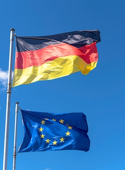 Bandeiras da alemanha e da união europeia contra o céu azul em berlim