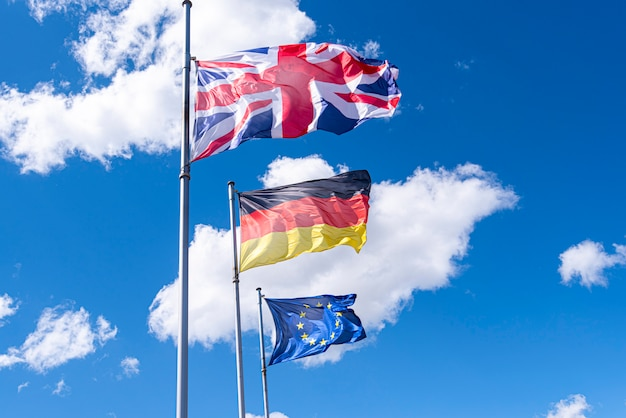 Bandeiras da alemanha, grã-bretanha e união europeia em uma rua. bandeiras da ue, reino unido e alemanha contra o céu azul
