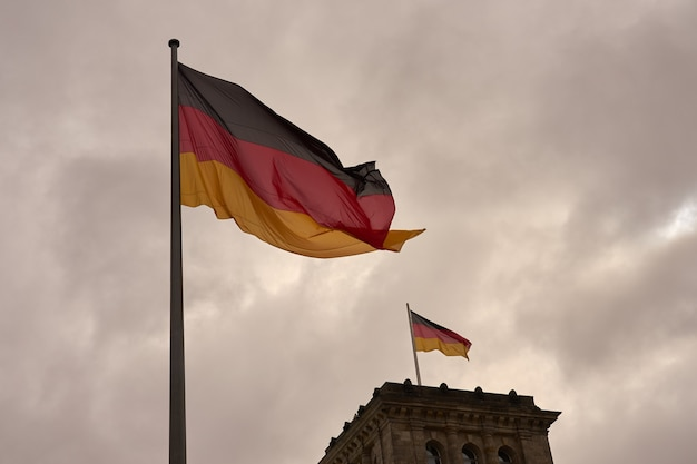 Bandeiras da alemanha no contexto de um céu nublado.