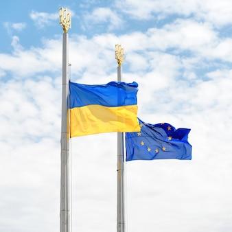 Bandeiras da europa e da ucrânia nos pólos com o céu azul como pano de fundo
