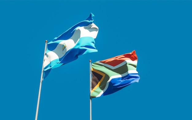 Bandeiras da nicarágua e da sar africana no céu azul. arte 3d