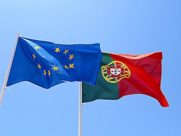Bandeiras da união portuguesa e européia ao gosto do vento.
