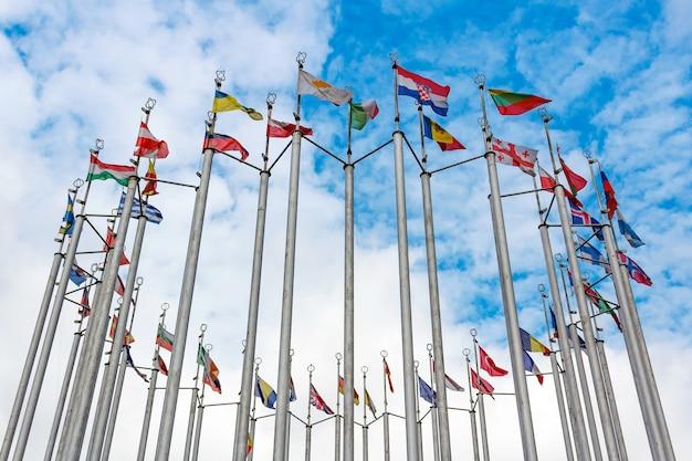 Bandeiras de diferentes países em mastros em uma rodada contra o céu azul