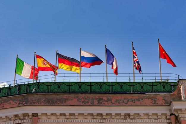 Bandeiras de diferentes países no telhado de um edifício ao vento contra