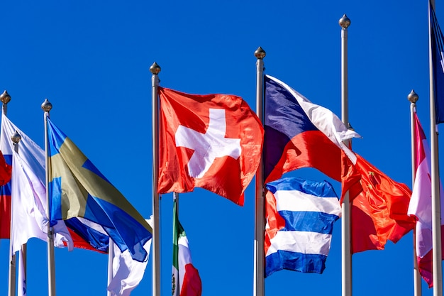 Bandeiras de diferentes países tremulam ao vento contra