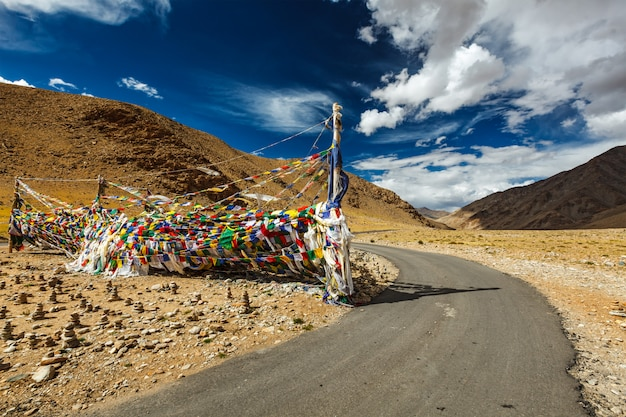 Bandeiras de estrada e oração budista lungta na passagem de namshang la. rapaz