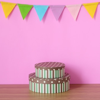 Bandeiras de festa coloridas na parede rosa e caixa de presente na mesa de madeira