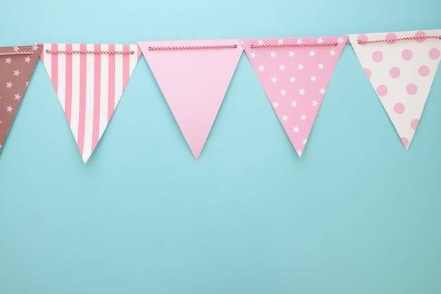 Bandeiras de festa de cor pastel sobre fundo azul