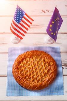 Bandeiras de mesa ao lado de torta redonda. bandeira da europa e eua. vamos compartilhar nossos valores. faça as pazes e coma a sobremesa.