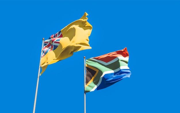 Bandeiras de niue e sar africano no céu azul. arte 3d