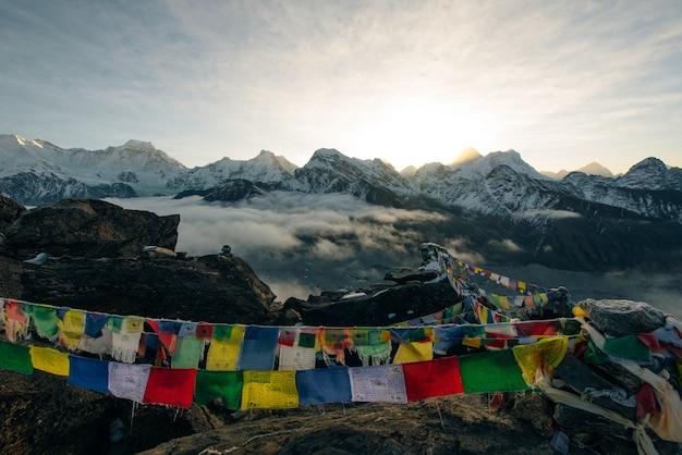 Bandeiras de oração budistas nas montanhas do himalaia, área do acampamento base de annapurna, no nepal.