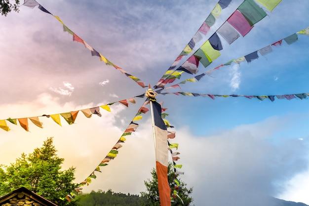 Bandeiras de oração tibetanas budistas contra o céu azul com uma nuvem com muitas bandeiras coloridas suspensas