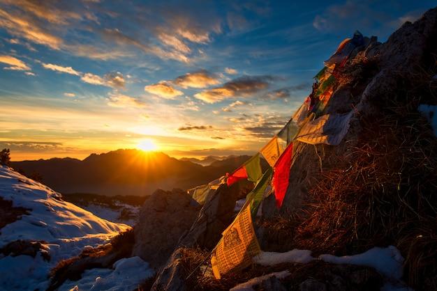 Bandeiras de orações tibetanas nas montanhas com as cores de um pôr do sol quente
