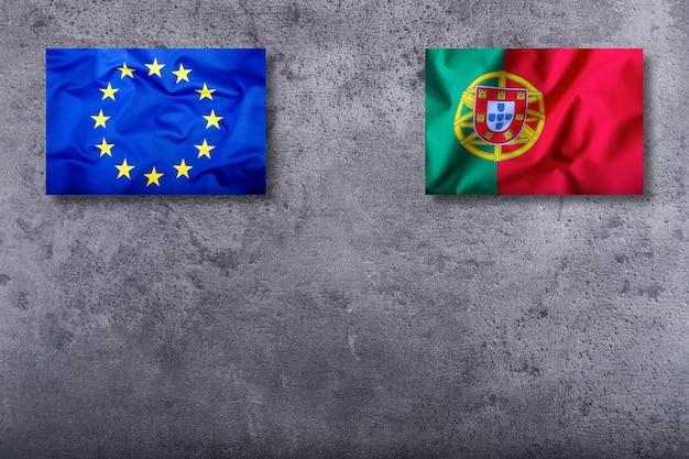 Bandeiras de portugal e da união europeia no fundo de concreto.