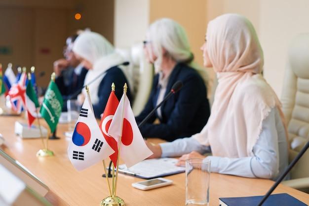 Bandeiras de vários países estrangeiros na mesa com fileiras de palestrantes interculturais participando da conferência