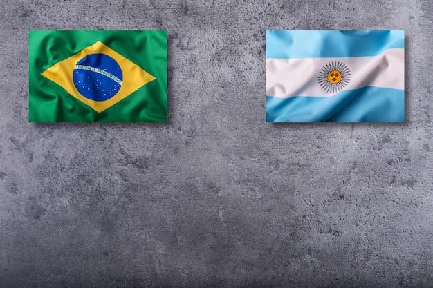 Bandeiras do brasil e da argentina em fundo de concreto.