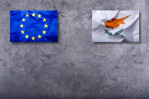 Bandeiras do chipre e da união europeia no fundo de concreto.