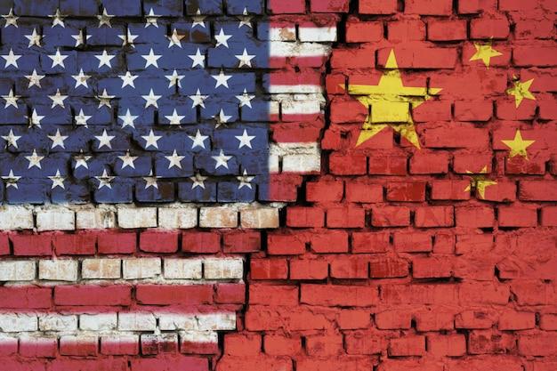 Bandeiras dos estados unidos e da china na parede de tijolos com grande rachadura no meio