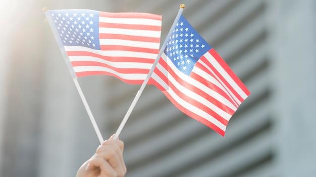 Bandeiras dos eua seguradas à mão