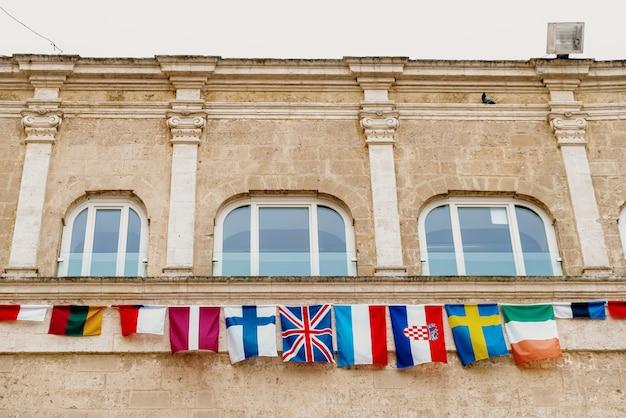 Bandeiras dos países europeus que penduram de um balcão na cidade italiana de matera.